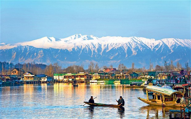 Shikaras on the famous Dal lake in Kashmir with a breath-taking view of snow clad Himalayas